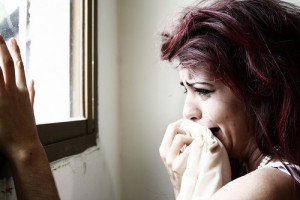 Photo of a woman crying into a cloth and looking out of a window