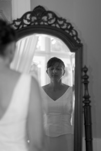Photo of a girl in a dress looking at herself in a mirror