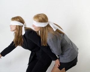 Photo of two women wearing blindfolds walking