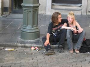 Photo of a teen couple sitting on sidewalk