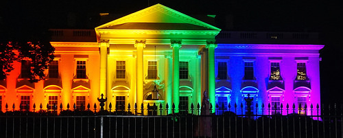 Photo of the White House lit with multicolored lights to form rainbow flag