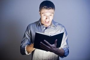 "Photo of a man reading a glowing book -heading image for ""What is the Best Study Bible Available?"""