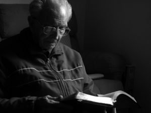 Photo of a man reading a Bible. Cover image for Myths About The Bible