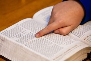 Photo of a child's hand pointing in a Bible