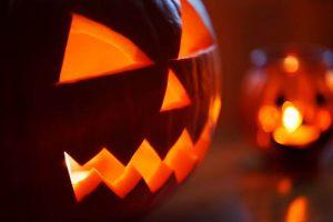Photo of a lit Jack-O-Lantern amidst a spooky background