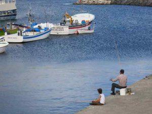 Photo of a man fishing on a beach with a boy sitting near him